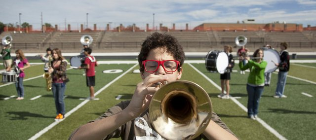 "Lawrence High junior trumpeter Jake Leet warms up with the marching band during practice Tuesday on the football field. Recently the band was awarded the prize of Grand Champion after winning the Blue Valley Invitational Tournament. The band has a theme this year of ""Caravan: A Journey Through the Sand."""