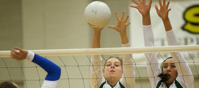 Free State's Mariah Dickson (11) and Marissa Thibodo (2) get up to block a spike attempt by Leavenworth's Crystal Simon. FSHS went 2-1 at a home quad Thursday.