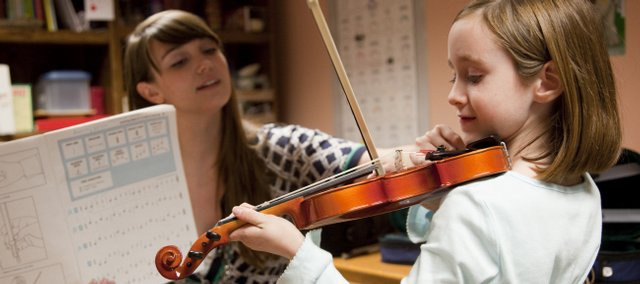 Nick Krug/Journal-World Photo.Aubrey Wilson, a Kansas University junior from Shawnee and Music Mentors volunteer, helps six-year-old Tatum McCart hold her violin properly during a lesson Tuesday, Oct. 6, 2009 at New York Elementary. Wilson is in her second year volunteering with the program.