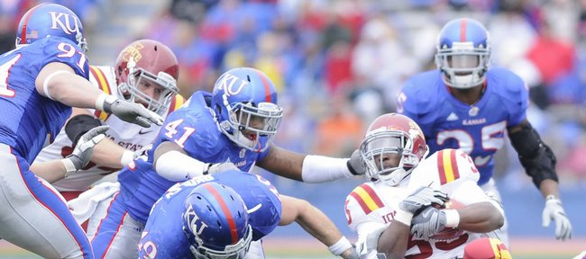 Kansas University defenders Drew Dudley (49), Justin Thornton (46), Arist Wright (41) and Jake Laptad (91) converge on Iowa State running back Alexander Robinson. Robinson rushed for a career-best 152 yards, and the Cyclones amassed 512 total yards, but the Jayhawks escaped with a 41-36 victory Saturday at Memorial Stadium.