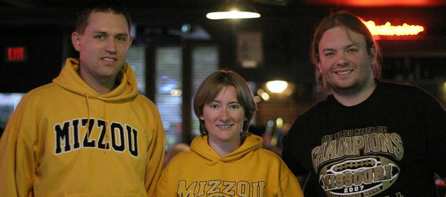 Robert Rescot, left, Tiffany Huggard-Lee and Charlie Huggard-Lee are among the University of Missouri alumni now in Lawrence who support both schools. They have talked of starting an alumni group for former Tigers.