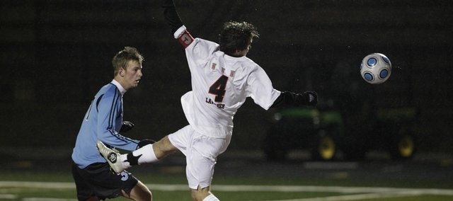 Lawrence High's Tor Forneli comes up just short on a header near the goal Tuesday in the Lions' loss against Shawnee Mission East.