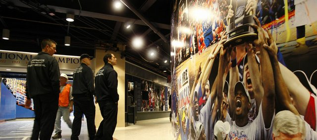 Lawrence-Douglas County Fire Medical workers stop to admire a wall of photographs from the Kansas University men's hoops 2008 national championship in the northwest corner of Allen Fieldhouse. The KU athletic department put on a tour of the renovations at the fieldhouse.