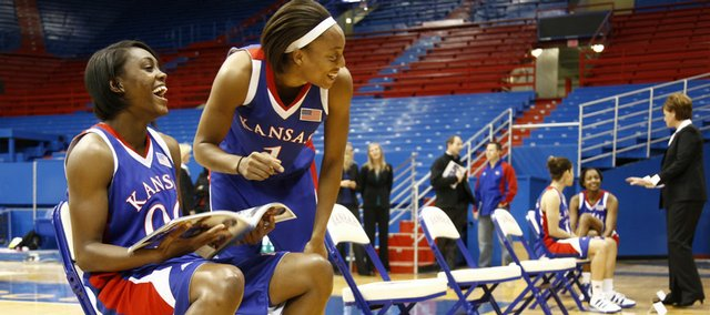 Kansas University teammates LaChelda Jacobs and Aishah Sutherland share a laugh as they browse the media guide on Wednesday in Allen Fieldhouse.