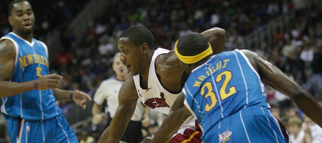 New Orleans forward and former Kansas player Julian Wright (32) tries to poke the ball away from former KU teammate Mario Chalmers of the Miami Heat during an exhibition game. The Heat won, 97-81, Thursday at the Sprint Center in Kansas City, Mo.