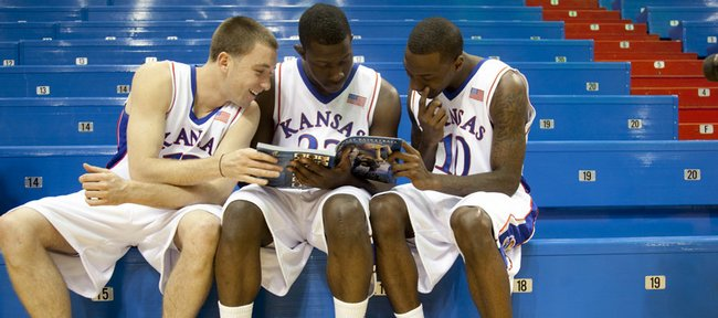 Kansas teammates, from left, Brady Morningstar, Mario Little and Tyshawn Taylor have a laugh as they peruse the media guide during Media Day on Thursday at Allen Fieldhouse.