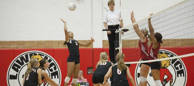 Lawrence High's Jasmyn Turner (5), center, prepares to deliver a point-winning spike against Emporia Tuesday during the Lion's Varsity meet.