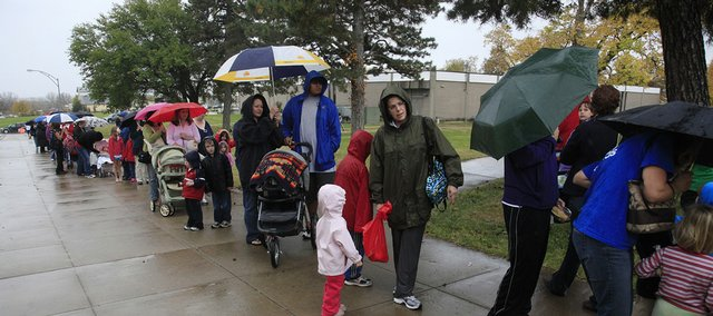 People wait in a light rain on Oct. 21, 2009, to get an H1N1 flu vaccination at Haskell Indian Nations University. It was the first H1N1 immunization clinic in Douglas County.