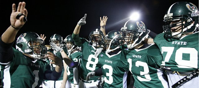 Free State quarterback Camren Torneden, left, directs his teammates in their school fight song after the Firebirds' fourth consecutive win over crosstown rival Lawrence High on Friday, Oct. 23, 2009 at Free State High School.