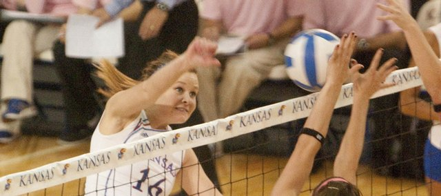 Kansas outside hitter Lauren Hagan, left, spikes against UMKC defenders. The Jayhawks swept the Roos on Tuesday at the Horejsi Center. Story on page 5B.
