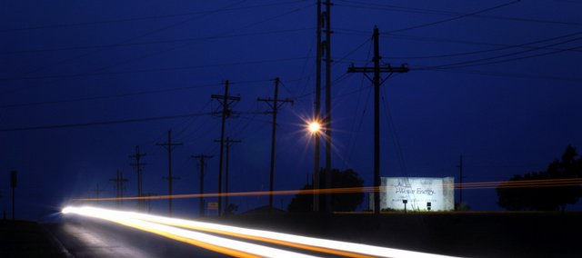 A vehicle's lights create a blur past the power lines and entrance to Westar Energy.