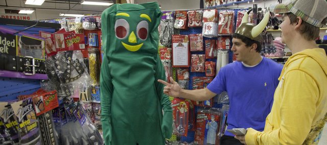 The Halloween spirit was alive and kicking Thursday afternoon at the Fun and Games costume store, 1601 W. 23rd St. Trying on a Gumby costume, Jake Miller gets opinions from his friends Ryne Laster, center, and Nick Scannapieco. Shoppers might be a little more frugal in their spending this year, but costume and candy sales won't be scrapped altogether.