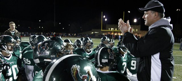 Free State head coach Bob Lisher applauds the Firebirds after a postgame talk following their 42-14 victory Friday over crosstown rival Lawrence High.