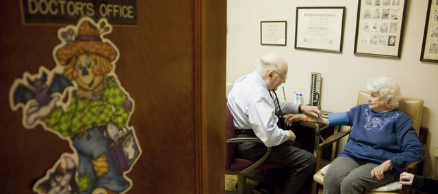 Dr. Philip L. Stevens treats a patient. Stevens has used only paper records in his 54 years of practice in Tonganoxie.
