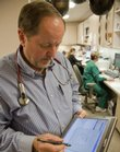 Dr. Steve Bruner of Lawrence Family Medicine & Obstetrics went paperless in 2003 and uses an electronic tablet to record and track patient information. He said the system has saved money and has improved patient care.