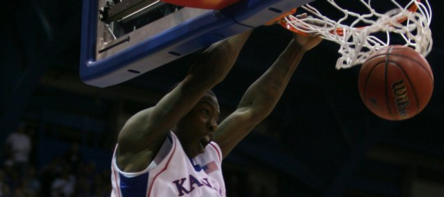 Kansas guard Elijah Johnson slams home an alley-oop over Fort Hays State guard Greg Schmidt on a pass from teammate Tyshawn Taylor during the second half of Tuesday's exhibition at Allen Fieldhouse.