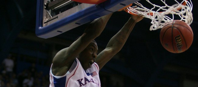 Kansas guard Elijah Johnson slams home an alley-oop over Fort Hays State guard Greg Schmidt on a pass from teammate Tyshawn Taylor during the second half of Tuesday&#39;s exhibition at Allen Fieldhouse.
