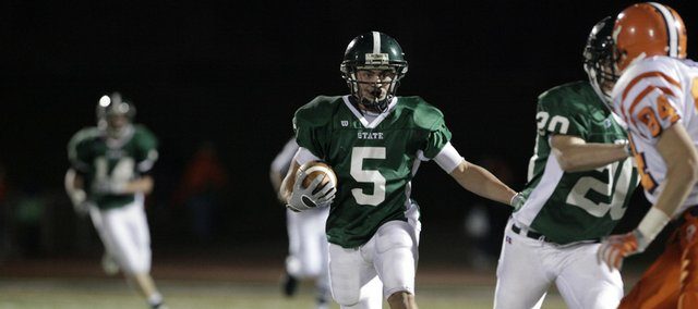 Free State safety Preston Schenck (5) scrambles for a few yards after intercepting an Olathe East pass in the fourth quarter. The Firebirds won the Class 6A first-round playoff game, 38-7, on Friday at Free State High.