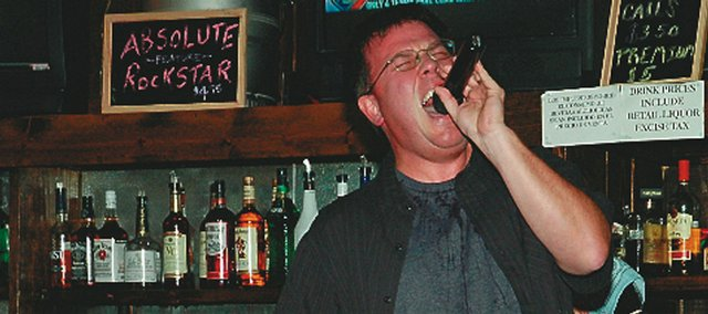 "Baldwin City resident Joe Bathke, atop the bar at Hickory Creek Barbecue, belts out his version of ACDC's ""Highway to Hell"" during a recent karaoke night performance."