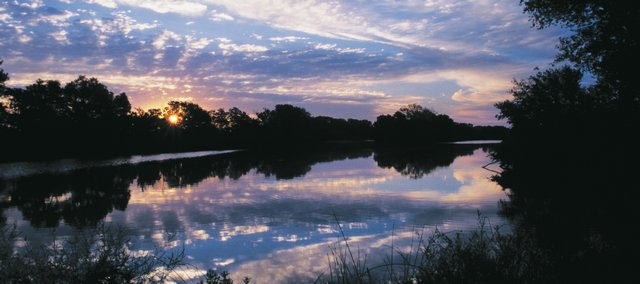 "A scene along the Ninnescah River, in southwestern Kansas. ""I watched the Ninnescah,"" Mike Blair writes. ""Its water flowed, and fish broke the surface. Drifting currents showed time in a different way. I understood life in a different way. Then the sky brightened, and it was time to go. When I left, I, too, was different."""