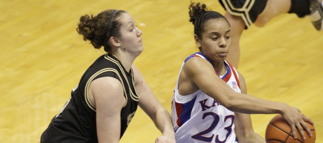 Kansas' Angel Goodrich (23) looks off an Emporia State defender before throwing a pass in the lane during a fast break. Goodrich had seven assists in the Jayhawks' 85-48 exhibition victory Sunday in Allen Fieldhouse.