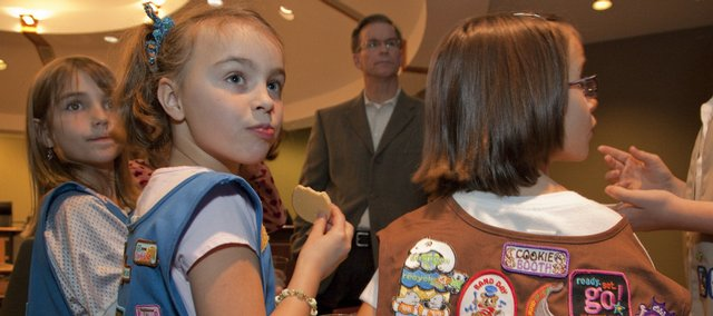 Lawrence Mayor Rob Chestnut, background, hosted a cookies and milk party at City Hall for the Lawrence Girl Scouts to let people know that cookie sales have begun. Gathering around the table on Tuesday were, from left, Daisy Scouts Isabel Mann and Lydia Storm and Brownie Scout Skyler Vanderbilt.
