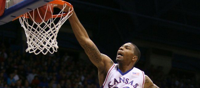 Kansas forward Marcus Morris delivers a powerful dunk sending Pittsburg State guard Andy Smith (14) to the floor during the first half Tuesday, Nov. 10, 2009 at Allen Fieldhouse.