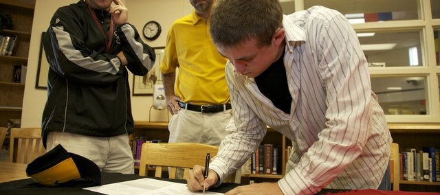 Lawrence High's Albert Minnis, right, signs his letter of intent to play baseball for Wichita State as LHS coach Brad Stoll, left, and Bryan Minnis look on.