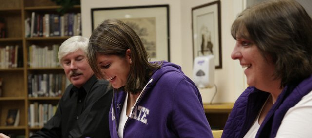 Lawrence High senior Shelby Miller, center, gathers with her father Doug, left, and mother Kay shortly before signing with Kansas State for a rowing scholarship on Thursday at the LHS library.