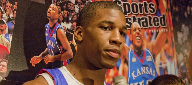 Kansas University freshman Thomas Robinson answers questions at a news conference on Thursday in Allen Fieldhouse. The power forward said one day, he'd like to be remembered on the same wall as Darnell Jackson and Mario Chalmers, pictured behind him.
