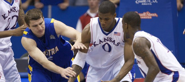 Kansas forward Thomas Robinson scrambles for a loose ball with Hofstra forward Miklos Szabo during the second half, Friday, Nov. 13, 2009 at Allen Fieldhouse. At right is Kansas guard Tyshawn Taylor.