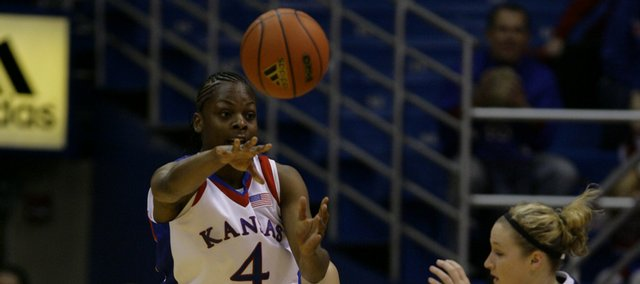 KU guard Danielle McCray (4) distributes the ball in first half action during KU's season-opening victory against Oral Roberts Sunday at Allen Fieldhouse.
