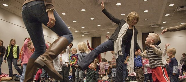 Doreen Cronin, award-winning childrens author, center right, danced with students Monday at the Lawrence Public Library as part of Kansas Reads to Preschoolers Week. The group participated in a mini-movement session with Danielle Lawrence, an instructor with Lawrence Parks and Recreation.