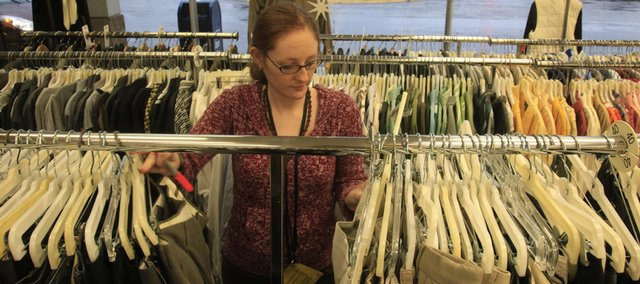 Kasey Lane, a worker at Lasting Impressions in The Malls Shopping Center, sorts through clothes for sale Tuesday. The shopping center at 23rd and Louisiana streets is celebrating a half-century in business this year. Lasting Impressions has been in the Malls for 20 years.