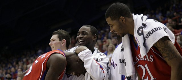 Kansas teammates Sherron Collins hugs Elijah Johnson, front, as the two laugh on the bench after Chase Buford's converted bucket after being fouled during the second half, Thursday, Nov. 19, 2009 at Allen Fieldhouse.