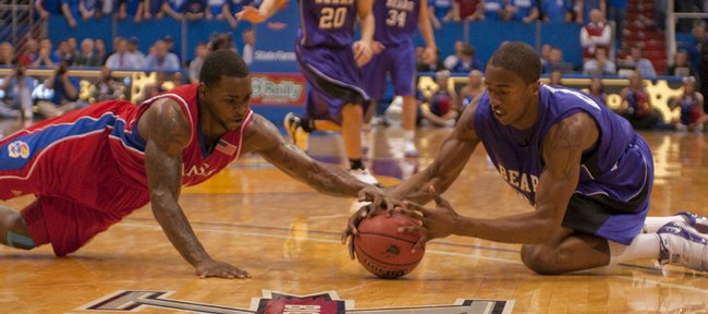 Sherron Collins (left) and Tadre Sheppard go for a loose ball during the second half action Thursday, Nov. 19, as Kansas defeated Central Arkansas 94-44.