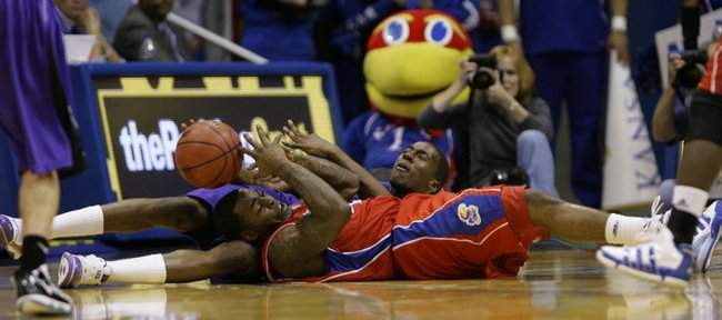 Kansas guard Sherron Collins and Central Arkansas forward Tadre Sheppard slide across the floor for a loose ball during the second half, Thursday, Nov. 19, 2009 at Allen Fieldhouse.