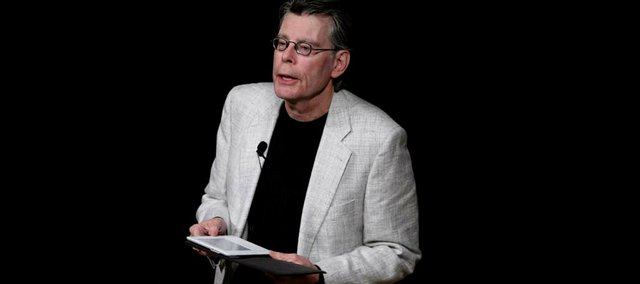 """Stephen King reads from his book """"Ur"""" with the Kindle 2 electronic reader at a news conference for Amazon.com in February."""