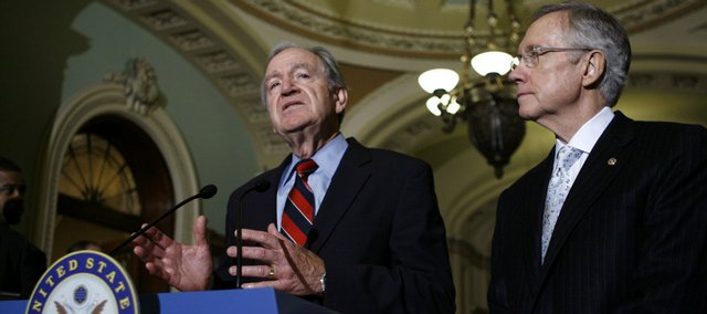 Sen. Tom Harkin, D-Iowa  speaks Saturday, Nov. 21, after the U.S. Senate voted to begin debate on legislation for a broad healthcare overhaul at Capitol Hill in Washington as Senate Majority Leader Harry Reid D-Nev., looks on.