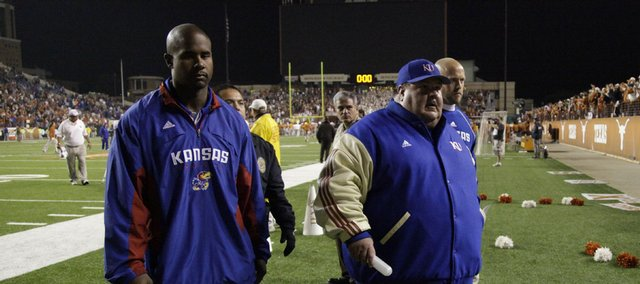 Kansas head coach Mark Mangino (right) walks off the field at Darrell K. Royal-Texas Memorial Stadium with coaching staff member Joe Vaughn following the Jayhawks' 51-20 loss to Texas.