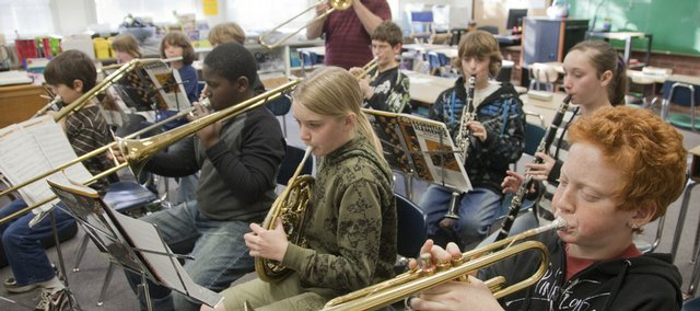 "David Wetrich, foreground right, a sixth-grader at New York School, rehearses ""Jingle Bells"" with the school band Monday. Standing at back is band instructor Paul Morgenroth. Gov. Mark Parkinson cut public schools on Monday by $36 million, in addition to not funding the $156 million needed to compensate for increased school costs. Since last year, base state aid has been cut from $4,433 per pupil to $4,012 per pupil. ""Some districts will be forced to lay off teachers and close schools,"" Parkinson said."