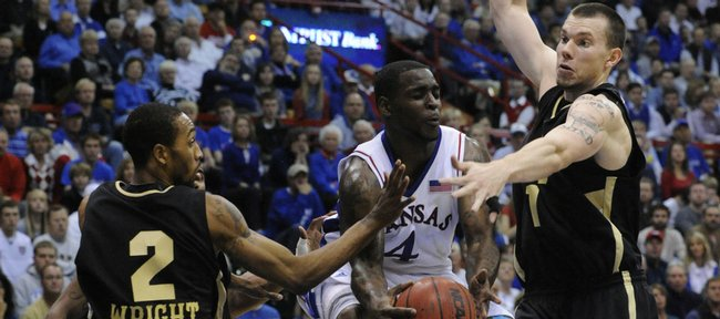 KU's Sherron Collins drives between Oakland defenders Larry Wright (2) and Derrick Nelson (1) during the first hal fWednesday, Nov. 25, 2009 at Allen Fieldhouse.