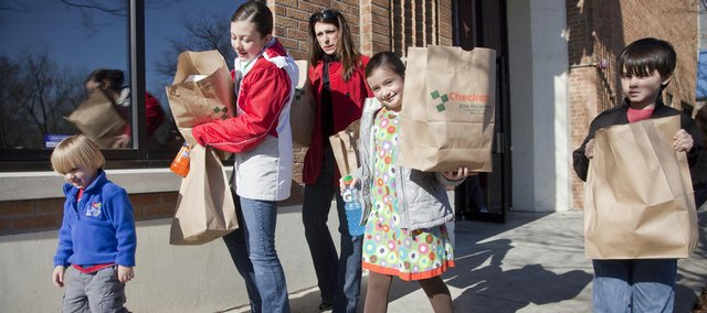 From left, Sam Stoll, 3; Maura Kennedy, 11; the children's aunt, Brandi Studer, Lawrence; Olivia Kennedy, 7; and Jack Stoll, 7, pick up 10 Lawrence Interdenominational Nutrition Kitchen Thanksgiving meals to deliver Thursday. About 400 in-home meals were delivered and prepared by volunteers in addition to the holiday LINK meal at First Christian Church.