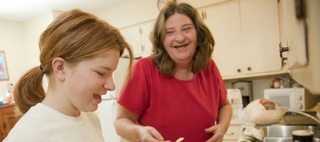 Roxanne Hutchinson laughs with her daughter Jasmine, 12, as the two make banana bread Wednesday in preparation for Thanksgiving in the kitchen of their Lawrence home. After becoming homeless in January, the mother and daughter stayed at various churches around Lawrence until finding a home through Lawrence Family Promise they moved into in April.