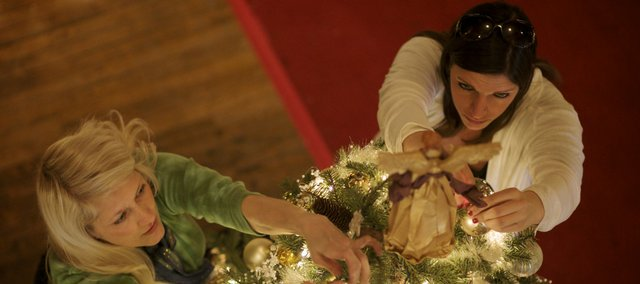 Angie Conrad, left, and Elsie Mohammadpour, both of Lawrence, put the finishing touches on their tree in preparation for the 2009 Festival of Trees at Liberty Hall.