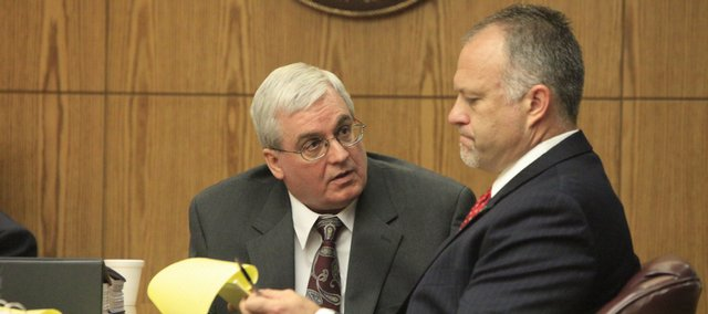 Defendant Arthur Davis III, left, and attorney Gregory Robinson chat about some notes Davis wrote during the first day of his trial Monday at Douglas County District Court.