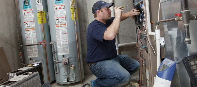 Chad Hull, a service technician with Cloud Heating, makes a service inspection in this 2009 file photo on a home gas furnace.