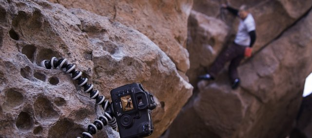 The Joby GorillaPod is a portable and versatile tripod that has flexible legs, making it easy to attach to virtually any surface. Here the GorillaPod SLR model supports a full-sized camera while clinging to a rock wall surface.