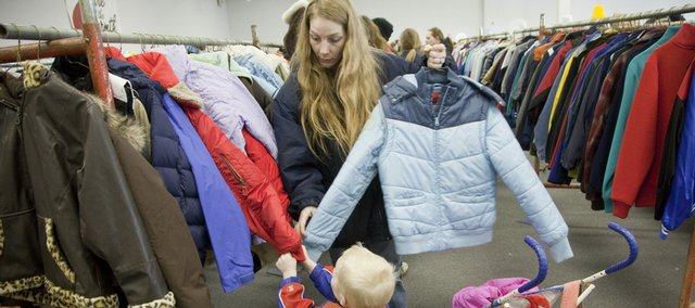 Betina Henshaw, Lawrence, checks out possible coats for herself with help from her son Joe Ladue, 3, at the Share the Warmth coat distribution Friday. The annual coat giveaway, supervised by the Salvation Army of Douglas County and sponsored by Scotch Fabric Care, continues today until noon at the I-70 Business Center, No. 119.