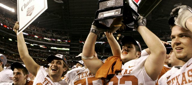 Texas players celebrate their 13-12 victory over Nebraska in the Big 12 Championship on Saturday in Arlington, Texas.